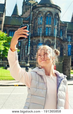 Cheerful young beautiful girl taking picture with smartphone in Glasgow historical place. Traveling. Summertime outdoors.