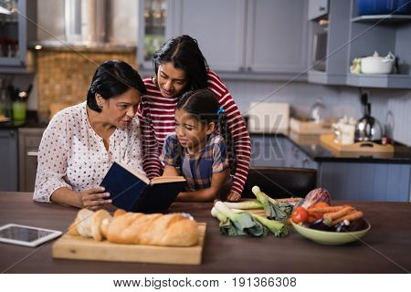 Multi-generation family sitting together in kitchen at home