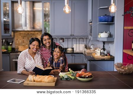 Portrait of smiling multi-generation family sitting together in kitchen at home