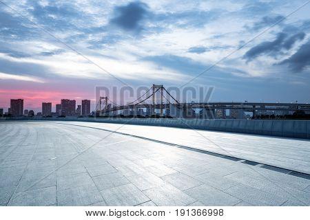 empty pedestrians sidewalk with modern suspension bridge in tokyo against cloud sky at twilight