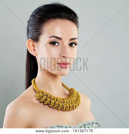 Perfect Young Woman with Jewelry Necklace on gray background
