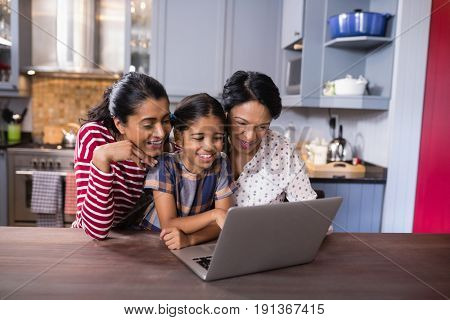 Smiling multi-generation family using laptop together in kitchen at home