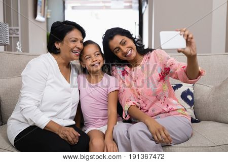 Happy multi-generation family taking selfie while sitting together at home