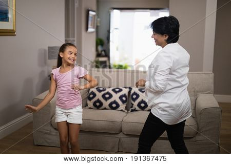 Smiling girl dancing with grandmother at home