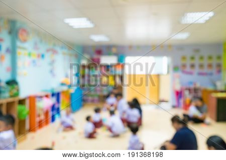 Blur image of student parent and teacher in kindergarten classroom Defocus of small kids playing in classroom vintage tone.