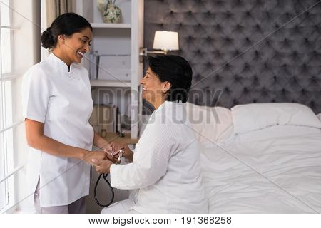 Smiling nurse comforting mature woman on bed at home