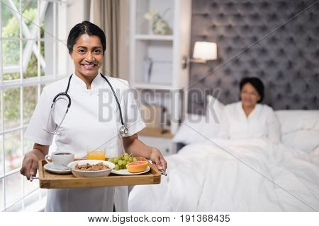 Portrait of smiling nurse holding breakfast tray while patient lying on bed at home