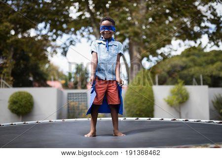 Full length of boy in superhero costume standing on trampoline