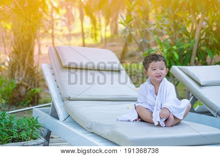 Asian Boy With White Towel Resting On A Lounge Deck Chair Or Sun Lounger Near Swimming Pool With Big