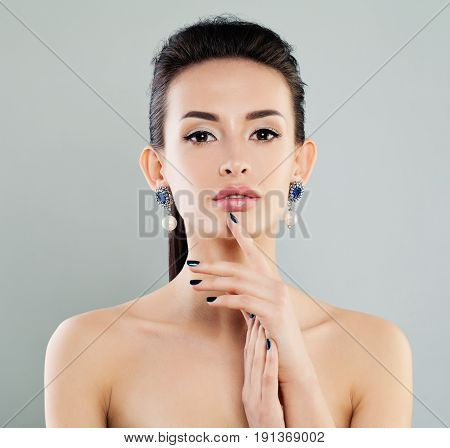 Beautiful Model Woman with Makeup Manicure and Earrings