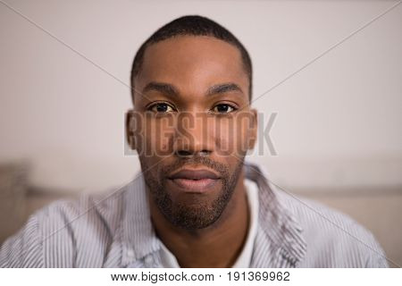 Close up portrait of confident young man at home