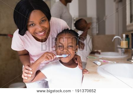 Portrait of smiling mother with daughter brushing teeth in bathroom at home