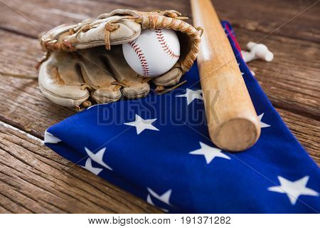 Close-up of baseball bat and gloves on an American flag