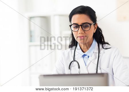 healthcare, technology people and medicine concept - female doctor in white coat with laptop computer at hospital
