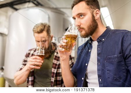 alcohol production, business and people concept - men drinking and testing craft beer at brewery