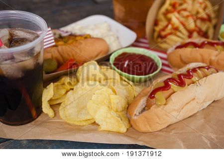 Close-up of snacks and cold drink on brown paper