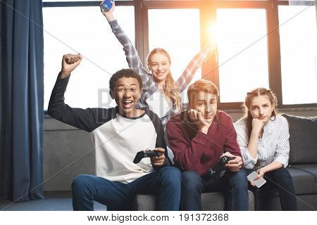 Happy Multicultural Teenagers Playing Video Games With Joysticks At Home, Teenagers Having Fun Conce
