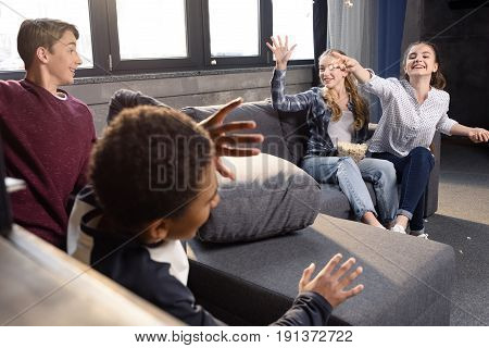Happy Group Of Teenagers Having Fun With Popcorn At Home