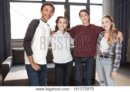 Happy group of teenagers standing together and smiling at camera indoors teenagers having fun concept