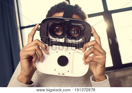 Close-up portrait of teenage boy wearing virtual reality looking at camera