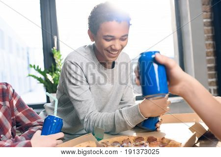 smiling teenage boy with soda drink and friends near by eating pizza at home concept