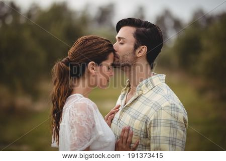 Boyfriend kissing girlfriend while standing on field at olive farm