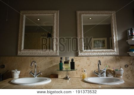 Mirrors hanging on wall by sink in bathroom at home