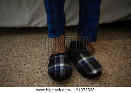 Low section of man by shoe on floor at home
