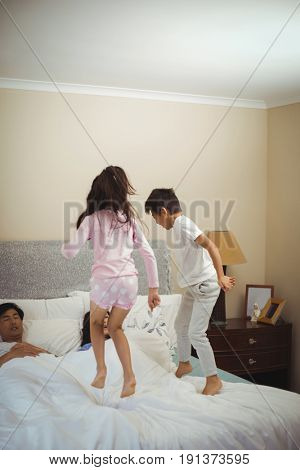 Siblings jumping on bed in bedroom at home