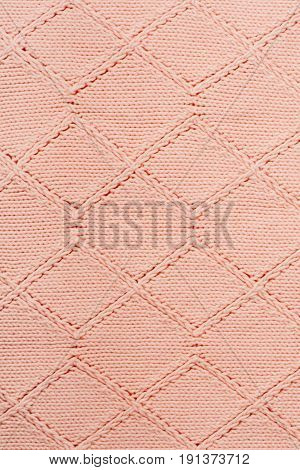 Sweater or scarf fabric texture large knitting. Knitted jersey background with a relief pattern. Wool hand- machine, handmade