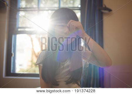 Girl waking up and rubbing her eyes in bedroom at home