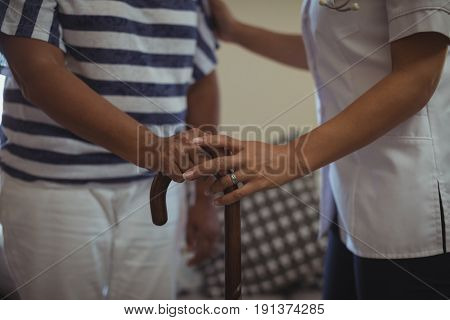Mid section of female doctor helping senior woman to walk with walking stick at home