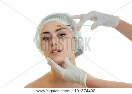 horizontal portrait of a young girl at the doctor who gloved introduces vaccine on face isolated on white background