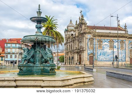 PORTO,PORTUGAL - MAY 13,2017 - Lion Fountain with churches Carmelitas and Carmo in Porto. Porto is located along the Douro river estuary in Northern Portugal.