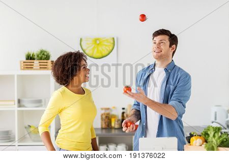 people, international and healthy eating concept - happy couple cooking food and juggling tomatoes at home kitchen
