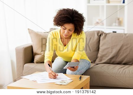 budget, finances and people concept - african american woman with papers and calculator counting money at home