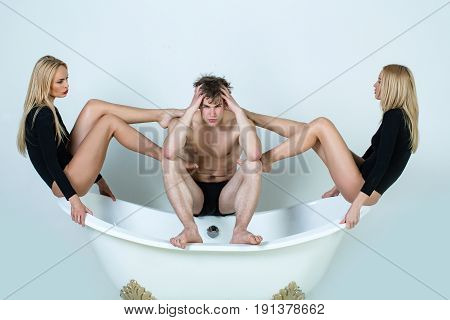 man choosing from women or sexy blonde girls with long legs in bodysuit sitting on bath tub on white background