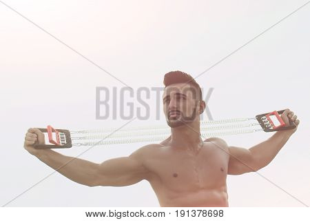 Expander In Hands Of Man With Muscular Body Workout