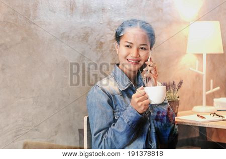 Beautiful young girl working at a coffee shop with laptop and coffee cup connecting internet telephone