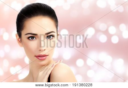 Closeup headshot portrait of a beautiful woman with beauty face and clean smooth soft skin, mild makeup. Abstract background with blurred lights