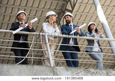 Team Of Contractors In Formal Wear Talking While Standing At Construction Site