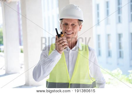 smiling mature constructor in professional equipment talking on walkie-talkie