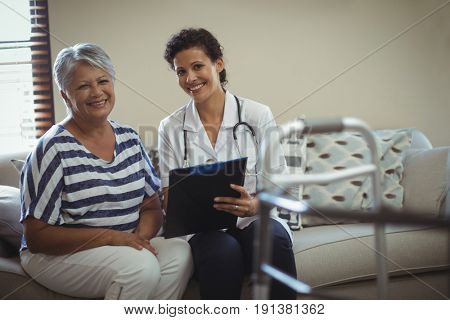 Portrait of female doctor with senior woman in living room at home