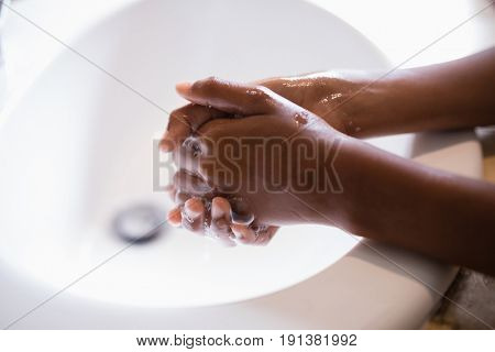 Cropped image of person washing hands at sink in bathroom