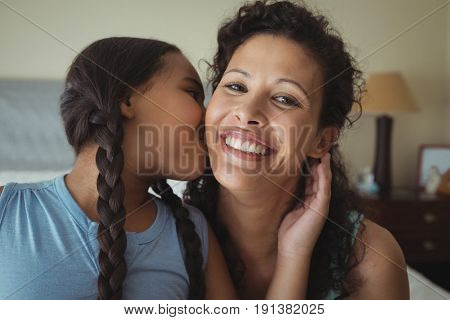 Daughter kissing mother on cheeks in bed room at home