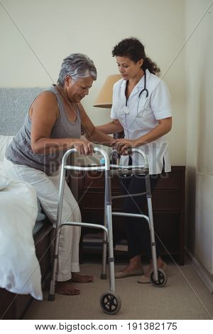 Female doctor helping senior woman to walk with walker at home