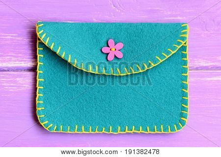 Children felt purse isolated on a wooden background. Purse made of felt using a decorative stitch and decorated with a pink button. Simple handmade crafts. Top view. Closeup
