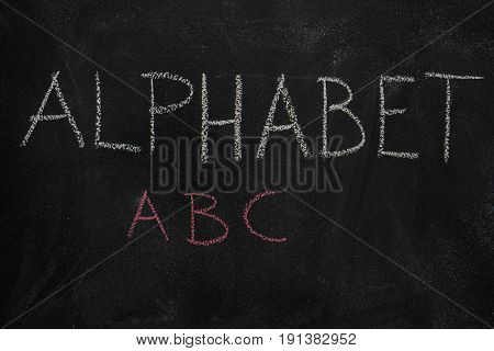 Alphabet word and first three letters written with chalk on blackboard. Education, school concept