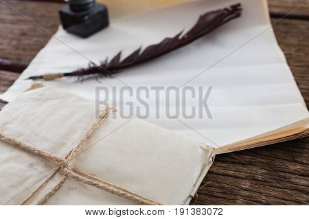 Quill feather, ink pot and legal documents arranged on wooden table