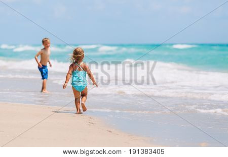 little girl and boy run play with waves on tropical beach